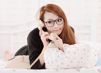 自宅で電話をする眼鏡の女性